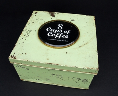 The 8 cups & saucers are housed in a vintage green metal bakery box